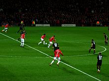 A wide shot of a football match with Manchester United in red in possession against Lyon in black.