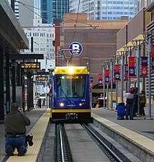 A light rail train with overhead electrification rolls toward the camera in an at-grade rail station.