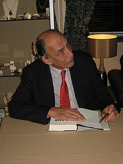 A man wearing a red tie with a chequered shirt and dark jacket signing a book