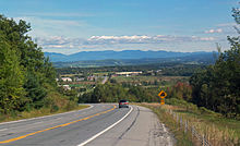 A road curving to the left with a car on it and a sign warning of a steep grade. It is descending toward a lower area with some buildings and another stretch of road. In the distance is a line of mountains.