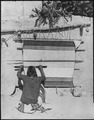 Navajo weaver spinning wool into yarn, full-length, seated, with a loom behind her, Torreon, New Mexico - NARA - 519159.tif