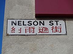 Signo legante Nelson Street, kun teksto en la ĉina sube.
