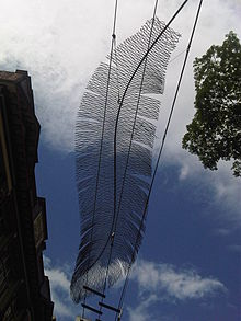 A wire sculpture shaped like a bird feather, silhouetted against the sky