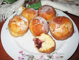 Six fried pampushky on a plate. Cherry filling is visible in one of them