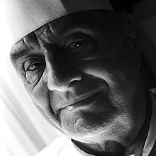 Black and white portrait of older man taken at a 45 degree slant filling the image field, his chef hat and coat are just visible