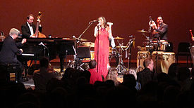 In the forefront is a crowd of people facing a stage. In the background are four people on a stage; a woman in the center is wearing a red dress and standing behind a microphone and the rest are men performing various instruments, including a piano, double bass and drum set.