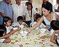 """President Gloria Macapagal-Arroyo enjoins one of the malnourished children to eat """"sopas"""" during a feeding program acitivity.jpg"""