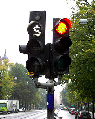 """Traffic-light signalling and operation - Swedish traffic light (left) for use by public transport vehicles only. All signals use white lighting and special symbols (""""S"""", """"–"""" and an arrow) to distinguish them from regular signals. The small light at the top tells the driver when the vehicle's transponder signal is received by the traffic light."""