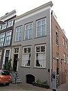 Hoekpand Nieuwkerkstraat. Gepleisterde lijstgevel met deurpartij, stoep en hek. Huis met oorspronkelijke gevel aan de Nieuwkerkstraat
