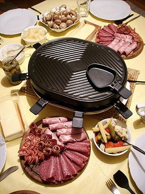 Raclette - A table-top raclette grill with typical accoutrements.