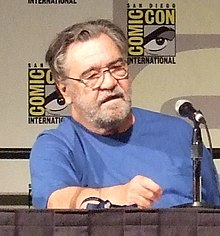 "Head and upper torso view of a lightly-bearded, middle-aged man in glasses and a plain t-shirt, sitting behind a table with a microphone on it.  Two small posters that read ""Comic Con International"" hang on the wall behind."