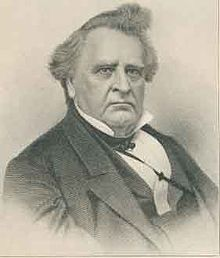 A portly, stern-looking man in his late fifties with graying black hair. He is wearing a white shirt and black jacket and facing right