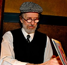 An elderly man with a white beard, round glasses, a beret-like hat, a dark vest, and a necktie. He faces down right, looking into an open book.