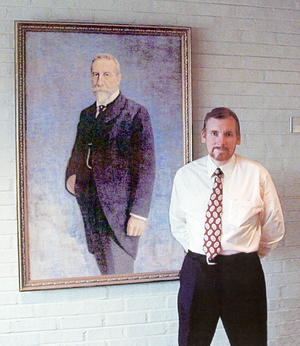 Robert C. Michelson - Robert Michelson next to a portrait of relative Christian Michelsen, at the Chr. Michelsen Institute in Bergen Norway.
