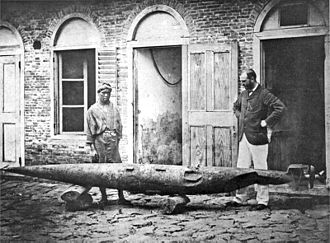 Torpedo - Robert Whitehead (right) invented the modern self-propelled torpedo in 1866. Pictured examining a battered test torpedo in Fiume c. 1875.