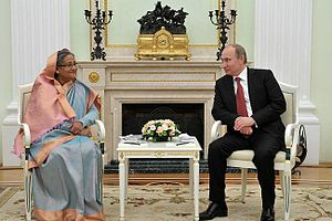 A seated Sheikh Hasina and Vladimir Putin smile at each other across a small table