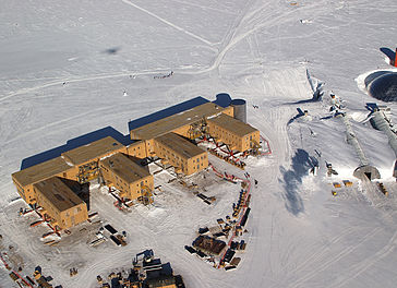 Amundsen-Scott South Pole Station. The ceremonial pole and flags can be seen in the background, slightly to the left of center, below the tracks behind the buildings. The actual geographic pole is a few more metres to the left. The buildings are raised on stilts to prevent snow buildup.