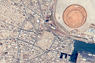 Sfax - A 2015 astronaut photo of Sfax.  Shown are the old city, part of the port, and the distinctive circular earth works of the  Taparura redevelopment project.
