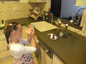 English: Girl lighting shabbat candles