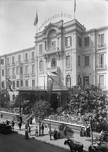 Period photo of a hotel, with four stories, large square windows, and a wrought iron portico with flags. Pedestrians, horse-drawn carriages and a motor car are before it