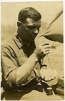 Soldier Using a Needle and Thread to Repair a Sock.jpg