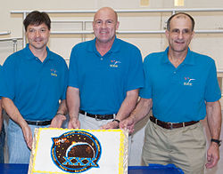 Soyuz TMA-03M crew during a cake-cutting ceremony.jpg