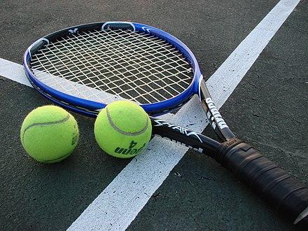 Теннисная ракета с мячами на теннисном корте.