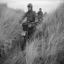 59th Divisional troops, on motorcycles, drive single-file cross country.