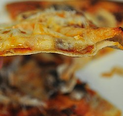 Side view of very thin pizza