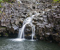 Trickle of a waterfall over basalt rocks on the road to Hana (8017230758).jpg