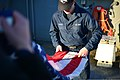 U.S. Navy Sonar Technician Seaman Terence Piper and another Sailor fold the U.S. flag aboard the guided missile destroyer USS Donald Cook (DDG 75) as the ship gets underway from Naval Station Norfolk, Va 140113-N-QM905-010.jpg