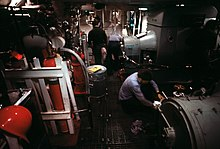 A large room with gray machinery visible on the right and gray and orange machinery visible on the left. Three men in light blue shirts and one man in a black shirt are working on the equipment.