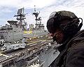 US Navy 030407-N-8933S-024 SSgt. Dan Jackson and Photographer's Mate 1st John Hudak circle above USS Iwo Jima (LHD 7) aboard a UH-1 Huey helicopter.jpg