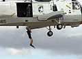 US Navy 040925-N-2347S-263 A search and rescue (SAR) swimmer demonstrates being lowered out of a UH-3 Sea King helicopter.jpg