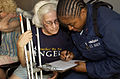 US Navy 050905-N-6436W-190 A U.S. Navy Sailor helps a Hurricane Katrina victim fill out paperwork after she was transported the dock landing ship USS Tortuga (LSD 46).jpg