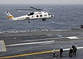 US Navy 060322-N-7981E-014 A Japan Maritime Self Defense Force (JMSDF) H-60J helicopter carrying Destroyer Squadron Nine, Commodore, Capt. Jeff Harley, lifts off from the flight deck aboard the Nimitz-class aircraft carrier USS.jpg