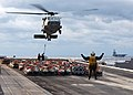 US Navy 070208-N-7571S-004 A Sailor Directs an MH-60S Seahawk, assigned to the Chargers of Helicopter Combat Support Squadron Two Six (HSC-26), during a Vertical Replenishment (VETREP).jpg