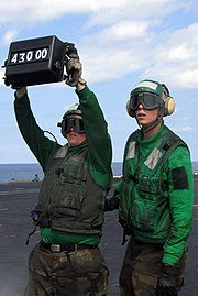 US Navy 080219-N-6326B-025 Aviation Boatswain's Mate (Equipment) Airman Ryan Martin, right, shows Aviation Boatswain's Mate (Equipment) Airman Nicoles Schulmeister how to properly signal with a weight board