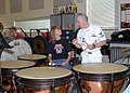 US Navy 080923-N-4649C-003 Storekeeper 3rd Class Stephen Hux gives pointers on playing the timpani to a student from McNary High School.jpg