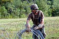 US Navy 090818-N-1580K-027 Builder 2nd Class Walter DeGracia, assigned to Naval Mobile Construction Battalion (NMCB) 22, lays concertina wire to form a defensive perimeter at the forward operating base.jpg