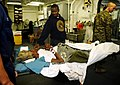 US Navy 100122-N-5345W-017 A 70-year-old Haitian woman is comforted by her son aboard USS Bataan (LHD 5).jpg