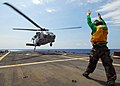 US Navy 100318-N-7058E-161 Aviation Structural Mechanic 3rd Class Nicholas Ellingson from Helicopter Sea Combat Squadron (HSC) 22 signals for an MH-60S Sea Hawk helicopter.jpg