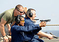 US Navy 100321-N-1082Z-049 Lance Cpl. Benjamin Stroope watches Operations Specialist 1st Class David L. Hesse and Information Specialist 2nd Class Wayne P. Mason during weapons qualification.jpg