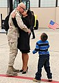 US Navy 111104-N-FJ200-060 Sailor receives a kiss from his wife during a homecoming celebration.jpg