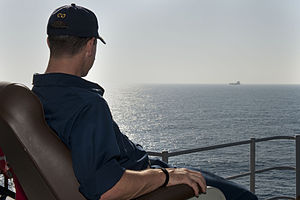 US Navy 111231-N-KS651-202 Cmdr. Homer Denius, commanding officer of the amphibious dock landing ship USS Pearl Harbor (LSD 52), watches a far off.jpg