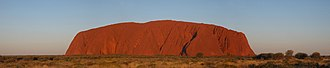 Uluru - Panorama of Uluru around sunset, showing its distinctive red colouration at dusk.
