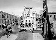 A period photo of street scene. Cars and pedestrians move through an intersection decorated with Union Jacks and Allied flags