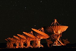 Orange light illuminates the array of dishes at night, with streaks of star-trails overhead.