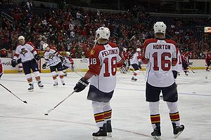 Two hockey players stand on the ice during pregame warm-up with their backs to the camera