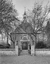 voorgevel met portaal en kerkhofhek met miniatuur-burchten van zandsteen op de hekpijlers - sint laurens - 20348980 - rce